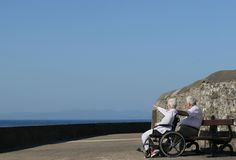 Elderly Twosome. Elderly woman in a wheelchair pointing at something in the distance and sitting next to an elderly man. Sea view and a blue sky in the Stock Photos