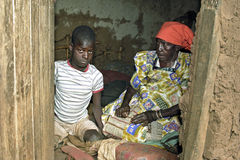 Elderly Ugandan woman cares for grandchild. Uganda, Luweero district, village Kalasa: a boy with a mental handicap is helped to dress by his grandmother Royalty Free Stock Photography