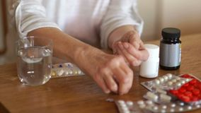 Elderly unrecognizable woman drinking a daily dose of pills with a glass of water. The hands of a person with arthritis.  stock video footage