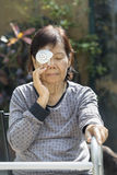 Elderly use eye shield covering after surgery. Stock Photos