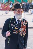 Elderly veteran of World War II walks outdoors. Tyumen, Russia - May 9. 2009: Victory Day in Tyumen. Elderly veteran of World War II walks outdoors royalty free stock images