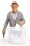 Elderly voter putting a ballot into a voting box Royalty Free Stock Images