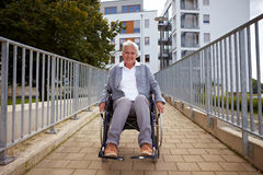 Elderly wheelchair user on ramp royalty free stock photography