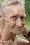 An elderly white-haired, unshaven man. Sadly looking at you Stock Photos