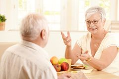 Elderly wife chatting to husband at breakfast Stock Images