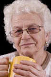 Elderly woman. Holding coffee or tea cup over black background Royalty Free Stock Photography