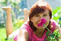 Elderly woman. Smells a flower Stock Photography