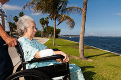Elderly woman. Elderly 80 plus year old women in a wheel chair convalescing outdoors in a bay setting Royalty Free Stock Photo