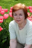 The elderly woman. The elderly woman sits near to tulips Royalty Free Stock Photos