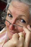 Elderly woman. A white caucasian woman holding her glasses on her nose Royalty Free Stock Photo