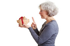 Elderly woman admonishing piggy Royalty Free Stock Photo