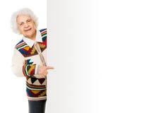 Elderly woman alongside of ad board Royalty Free Stock Photos