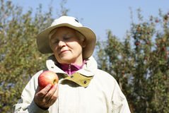 An elderly woman with apple Stock Photography
