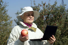 An elderly woman with an apple and a laptop. In the autumn garden Royalty Free Stock Photography
