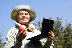 An elderly woman with an apple and a laptop. In the autumn garden Royalty Free Stock Photos