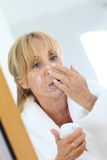 Elderly woman applying daily cream on her skin Royalty Free Stock Images