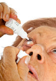 Elderly woman applying eye drops Stock Images