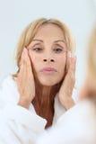 Elderly woman applying facial cream Stock Photography