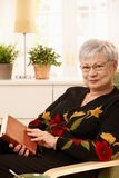 Elderly woman in armchair with book Royalty Free Stock Photo