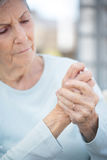 Elderly woman with arthritis. Elderly woman rubbing her hands having problems with arthritis royalty free stock photos