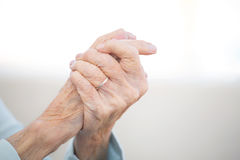 Elderly woman with arthritis. Elderly woman rubbing her hands having problems with arthritis royalty free stock photography