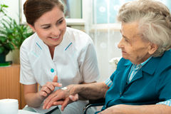Elderly woman is assisted by nurse at home Stock Photos