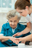 Elderly woman is assisted by nurse at home Royalty Free Stock Photos