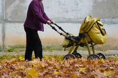 Elderly woman with a baby carriage. walking on yellow foliage. Elderly woman riding a stroller on the sidewalk of an empty road in stock image