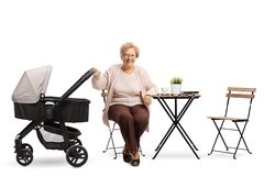 Elderly woman with a baby stroller sitting at a coffee table royalty free stock photography