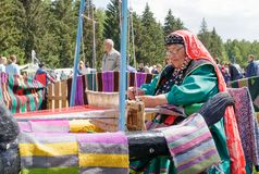 An elderly woman in Bashkir clothes is seated at a old wooden oom and weaves a carpet. National holiday Sabantuy in the city park stock image
