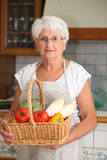 Elderly woman with basket of vegetables Stock Image