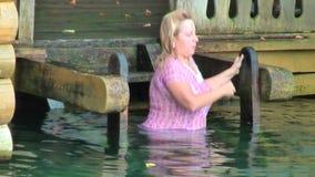 Elderly woman bathes in Sarov St.Seraphim Source stock footage