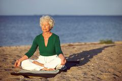 Elderly woman on beach meditating by ocean Royalty Free Stock Images