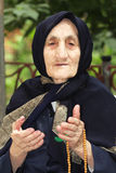 Elderly woman with beads gesticulating stock photos