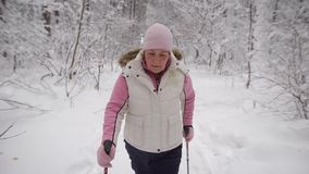 Elderly woman in a beautiful sports wear is engaged in Nordic walking on  snowy path in winter forest. Modern pensione stock video