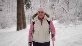 Elderly woman in a beautiful sports wear is engaged in Nordic walking on  snowy path in winter forest. Modern pensione stock video footage