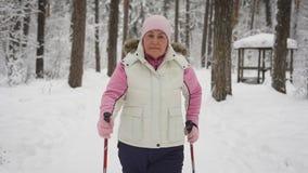 An elderly woman in a beautiful sports wear is engaged in Nordic walking on a snowy path in winter forest. Modern stock footage