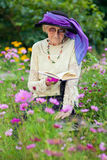 Elderly woman in a beautitul hat sitting reading Stock Photo