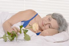 Elderly woman in bed with rose Royalty Free Stock Image