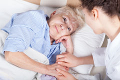 Elderly woman in bed. Elderly women in bed and her nurse royalty free stock image