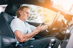 Elderly woman behind the steering wheel using her phone royalty free stock image