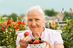 Elderly woman with berries. Elderly smiling woman sitting on the terrace, holding a bowl with strawberry and cherries Royalty Free Stock Photo