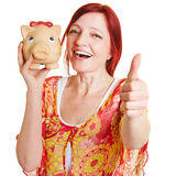 Woman with piggy bank holding. Elderly woman with big piggy bank holding her thumbs up Stock Photos