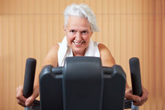 Elderly woman on bike in gym Stock Photos