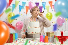 Elderly woman with a birthday cake blowing a party horn. Against a wall with balloons and decoration flags royalty free stock images