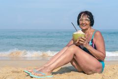 An elderly woman with black hair sits by the sea on a sunny day. A woman in a bathing suit with a coconut is smiling royalty free stock images