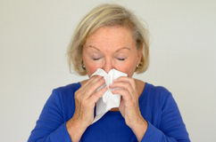 Elderly woman blowing her nose Stock Photography