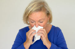 Elderly woman blowing her nose Royalty Free Stock Image