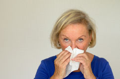 Elderly woman blowing her nose Stock Images