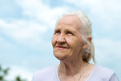 Elderly woman at the blue sky background. Elderly lovely woman at the blue sky background Royalty Free Stock Image